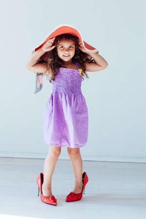 Photo pour Beautiful little fashionable girl in dress and moms shoes - image libre de droit