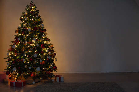 Photo pour Christmas tree with gifts of garland lights at night on New Years Eve in the interior room - image libre de droit