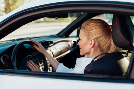 Photo for Beautiful female blonde driver behind the wheel of a car on the road - Royalty Free Image