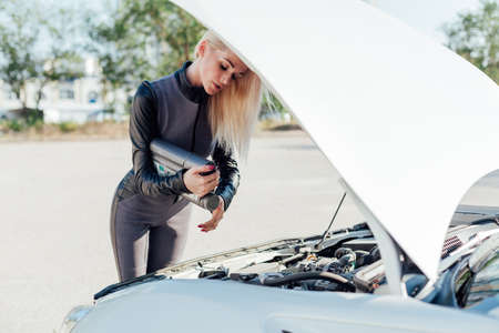 Photo pour Beautiful blonde woman on the road repairs the engine of a white car - image libre de droit