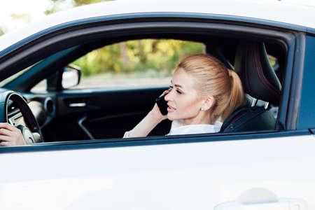 Photo pour Beautiful female blonde driver talking smartphone behind the wheel of car - image libre de droit
