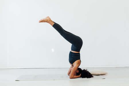 Photo pour Beautiful brunette woman yoga asana gymnastics fitness stands on her head - image libre de droit