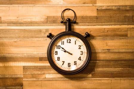 Foto de Old authentic clock hanging on a wooden wall. - Imagen libre de derechos