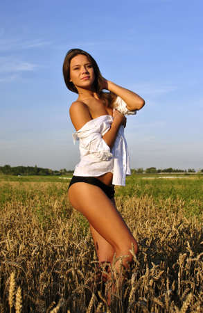 sexy girl in white shirt posing in the field