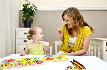 little girl and mom playing in a children puzzle