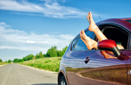 Woman's legs out of the car window. Concept of carefree funny trip.