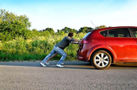 Man and woman pushing a broken car