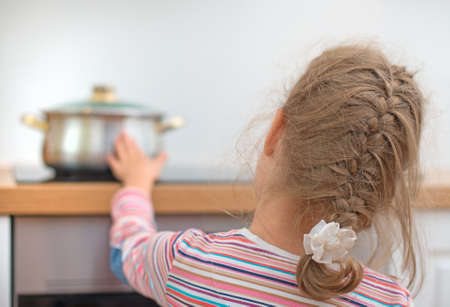 Photo pour Little girl touches hot pan on the stove.  Dangerous situation at home   - image libre de droit