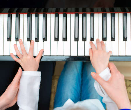 Photo for Woman teaching little girl to play the piano. Top view. - Royalty Free Image