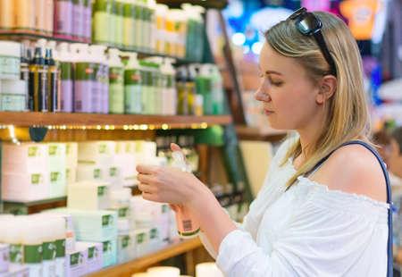 Photo pour Young woman choosing cosmetic cream in beauty shop. - image libre de droit