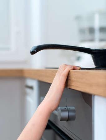Photo pour Child touches hot pan on the stove. Dangerous situation at home. - image libre de droit
