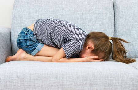Photo for Sad little girl crying on the sofa. - Royalty Free Image