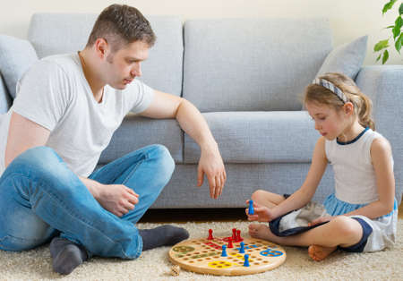 Photo pour Little girl and her father playing ludo. - image libre de droit