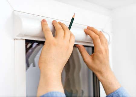 Photo pour Man installing cassette roller blinds on windows. - image libre de droit