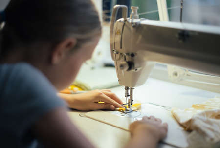 Photo pour Little girl working on sewing machine at home. Close-up view. - image libre de droit