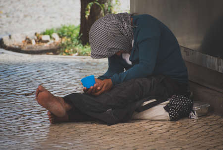 Photo for Homeless woman begs alms in the street. - Royalty Free Image