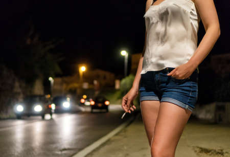 Foto de Prostitute with cigarette waiting for the client at night street. - Imagen libre de derechos