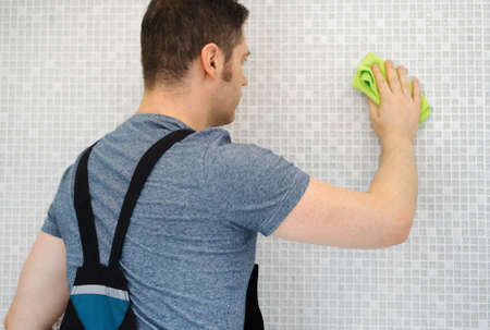 Photo for Tiler cleaning mosaic tiles in bathroom after repairs. - Royalty Free Image