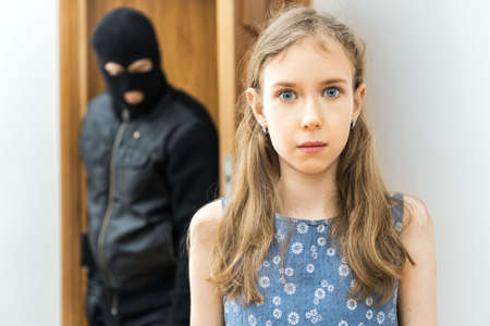 Photo for Shocked little girl and angry robber in the background. - Royalty Free Image
