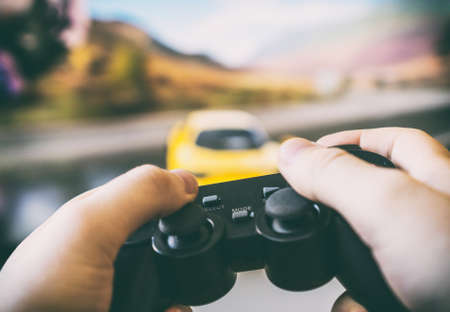 Photo pour Man playing racing video game on TV. Gamepad controller in hands. - image libre de droit