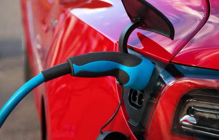 Photo pour Electric plug charging red sports electric car. - image libre de droit