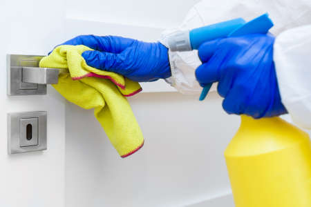 Photo pour Hand in protective glove with rag cleaning door handle. - image libre de droit