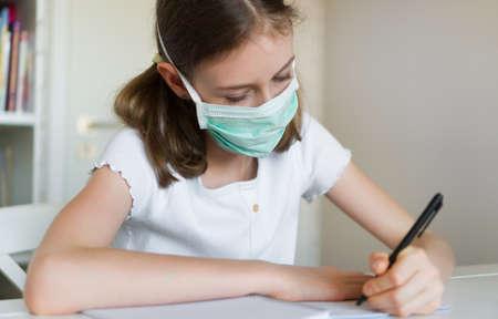 Photo pour Little girl doing school homework during quarantine. - image libre de droit