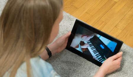 Photo pour Teacher watches as girl plays the piano. Home schooling. - image libre de droit