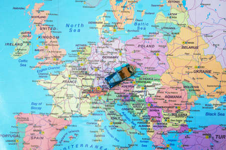 Photo pour Small toy retro car in the middle of Europe map. Travel by car concept. - image libre de droit