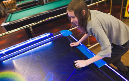 Photo for Tween girl plays air hockey in the entertainment center. - Royalty Free Image