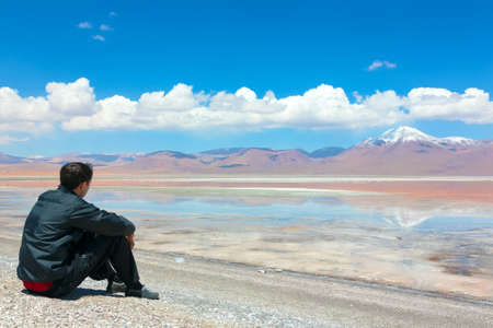 Young man sitting alone on the shore of Laguna Colorada, Bolivia