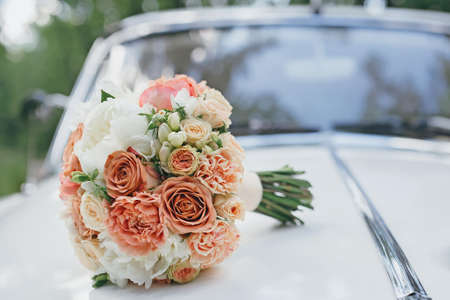 Photo pour Wedding bouquet on the hood of a white retro car - image libre de droit