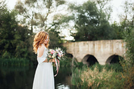Photo pour The bride with a bouquet on beautiful large lake background at sunset. Rustic Wedding - image libre de droit