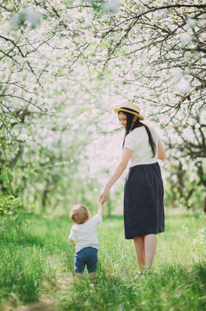 Photo pour Little baby boy with her young mother in the blossom garden - image libre de droit