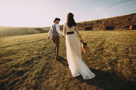 Photo pour Happy husband and wife. Wedding day. Beautiful nature. Walk during the photo session. They smile at each other. Holding hands - image libre de droit