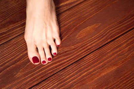 Foto de female legs with hands with manicure and pedicure on the wooden floor. - Imagen libre de derechos