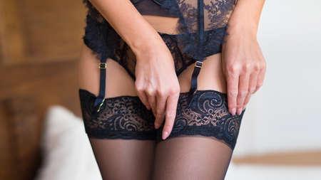 Foto de Beautiful female legs in black stockings with garter in a bedroom interior - Imagen libre de derechos