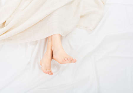 Photo pour Female feet under blanket flat lay. Female beautiful feet with red pedicure on the bed. Top view on the sleeping woman legs under blanket - image libre de droit
