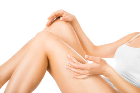 Photo pour Woman touching her leg with a perfect glowing skin. Skin care concept. Isolated on white. - image libre de droit
