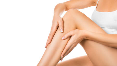 Photo pour Woman applying moisturizer on her perfect legs, isolated on white background. Skin and body care concept - image libre de droit