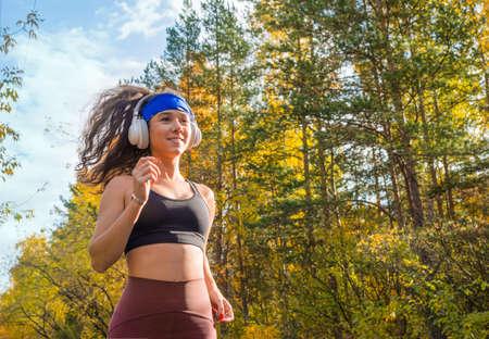 Woman jogging outdoor. Close up side portrait. Autumn