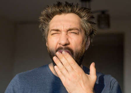 Photo for Man with a beard after waking up yawns, looking at the morning sun. - Royalty Free Image