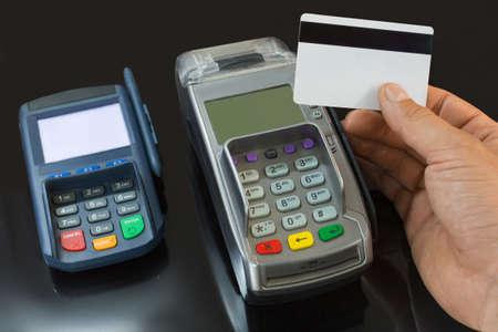 Photo pour A male hand holds a payment card above the payment terminal. - image libre de droit