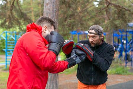 Foto de Middle-aged boxer training with coach. - Imagen libre de derechos