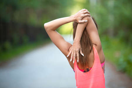 Foto de Sport and healthy lifestyle concept - woman warming muscles before workout. Back view, - Imagen libre de derechos