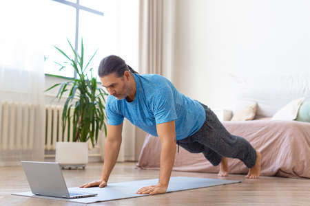 Foto de Middle-aged man doing push-ups in front of laptop. He uses an online tutorial from the internet to monitor the workout. - Imagen libre de derechos