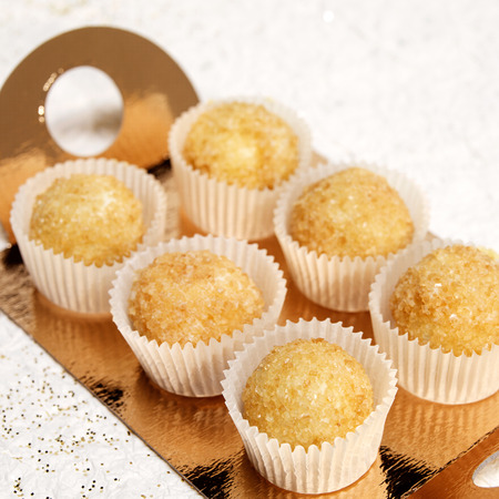 Six traditional muffins in paper forms on a gold support