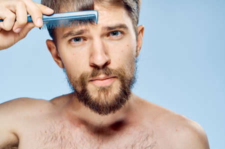 Young guy with a beard on a light background holds a comb.