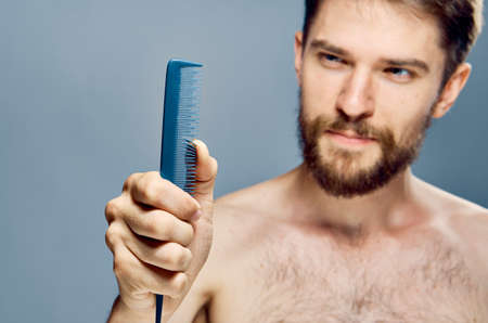 A young guy with a beard on a gray background holds a comb.