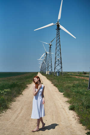 Beautiful young woman in a white dress in a field near a windmill.